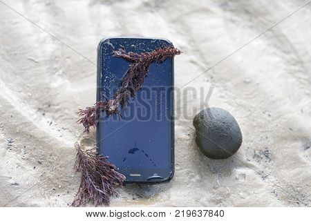 Mobile phone submerged in the water, sand and seaweed on the cell phone, lost on the beach