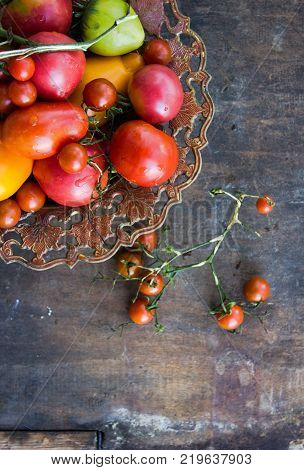 Cherry tomatoes in a copper bowl. Colorful tomatoes Tomatoes background. Fresh tomatoes Healthy food concept. Colorful festive still life. Loosely laid tomatoes in different positions. Copyspace
