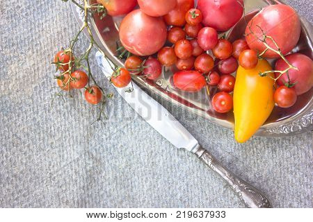 Colorful tomatoes red tomatoes yellow tomatoes orange tomatoes green tomatoes. Tomatoes background. vintage stone background
