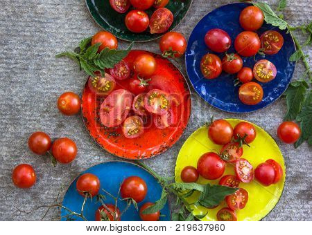 cherry tomatoes in multi-colored copper plates. view from above. Colorful tomatoes red tomatoes yellow tomatoes orange tomatoes green tomatoes.