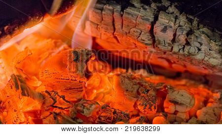 Fire fireplace ember wood home Embers closeup. Glowing embers in hot red color.