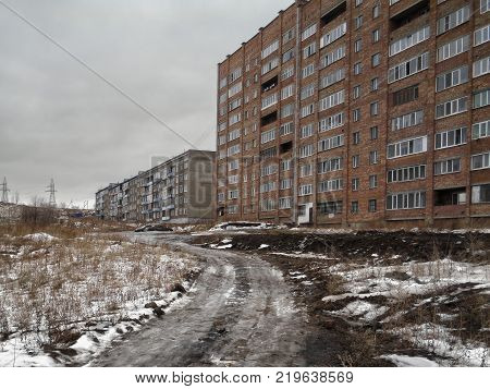 Grunge urban landscape. City outskirts. Thaw. Apartment buildings