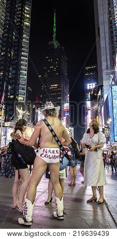 Times Square, New York City, New York, United States - circa 2015 -  naked cowboy in underwear with guitar singing and playing for tourists in times square night new york city
