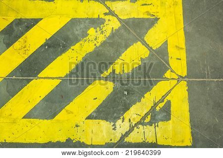 Close up yellow stripes prohibiting parking on grey surface