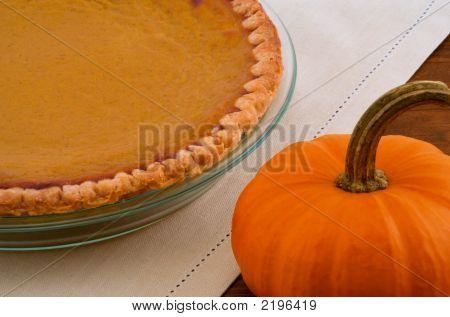 Pumpkin Pie And Pumpkin On Wood Table