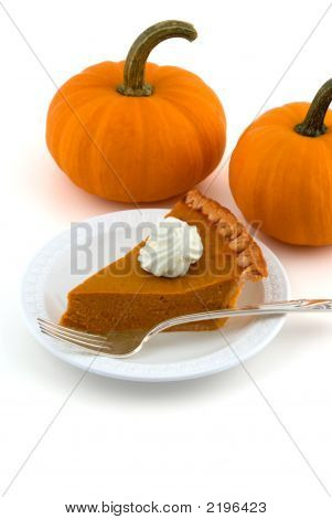 A Slice Of Pumpkin Pie With Two Pumpkins Isolated On White