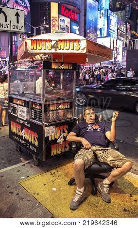 Times Square, New York City, New York, United States - circa 2015 - peanut vendor wearing I Love New York tee shirt and slouched in chair on sidewalk next to vendor cart in times square night new york city