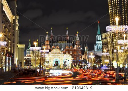 12.24.2017. Moscow. Russia. Moscow Kremlin at night on the eve of the New Year. Main road with cars passing by it. Transport in motion along the Tverskaya street.
