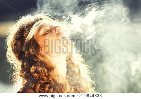 Beautiful Free Hippie Girl Blowing Smoke - Vintage Effect Photo