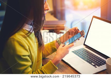 Cropped image of young hipster girl reading notification on smartphone while working on freelance