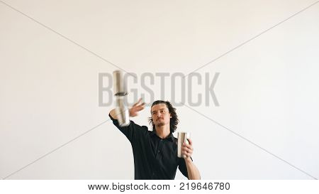 Professinal bartender man juggling bottles and shaking cocktail at mobile bar table on white background studio indoors