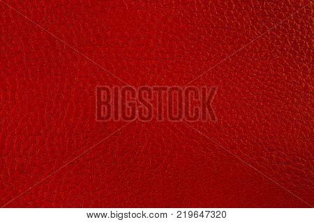 Artificial leather. Fine relief texture. Background or backdrop of red leatherette.