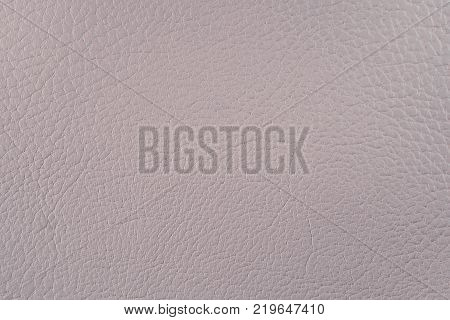 Artificial leather. Fine relief texture. Background or backdrop of beige leatherette.