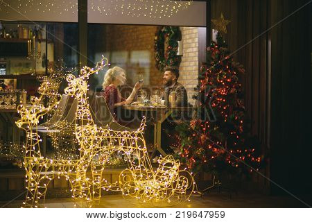Happy family celebrate new year and christmas. Couple in love enjoy xmas cuisine food wine. Woman and man in restaurant with festive decorations. Winter season romance. Holidays celebration concept.