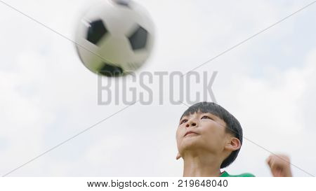 Asian teenage player jumping & heading soccer outdoors in the air