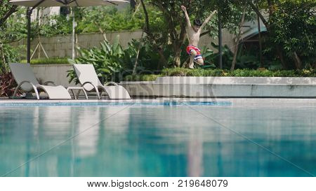 Asian teenage boy jumping up and falling down into the outdoor swimming pool