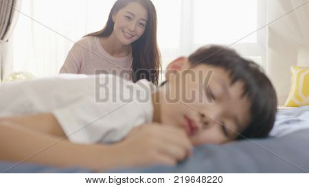 smiling Asian mother looking at his son in sleep in the morning