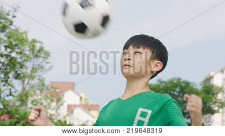 Asian teenage soccer player preparing to stop the ball with chest outdoors