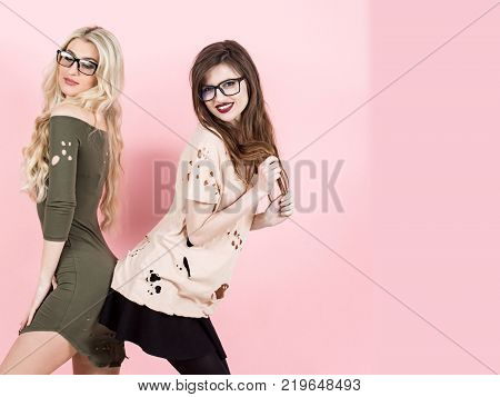 Women with long hair smile in geek glasses. Girls pose in torn clothes on pink background. Visage makeup hairstyle. Fashion style vogue. Beauty look concept copy space