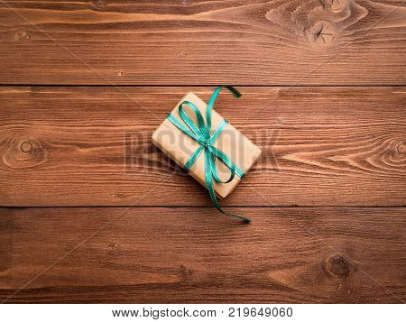 Gift box with green ribbon on the center wood antique rustic brown table. A surprise gift in brown Kraft paper