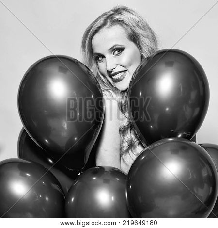 One beautiful smiling flirtatious young happy blond woman with long curly hair standing in bunch of red party balloons in studio on yellow backdrop square picture