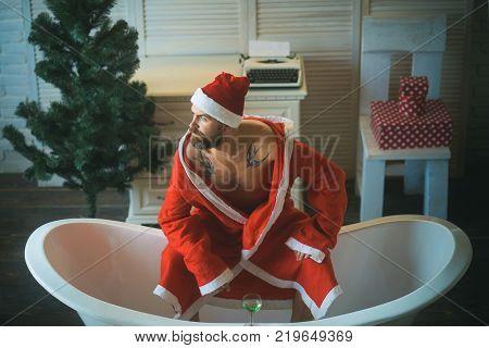 Winter holiday and xmas party. Expectation love and betrayal. Christmas man with beard waiting. Home alone bad santa in bath. Hipster santa at Christmas tree drink wine loneliness.