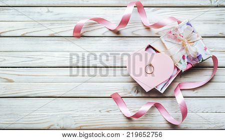 Marriage proposal concept. A wedding ring in a gift box on a wooden background. Valentine's Day. Marriage proposal concept.
