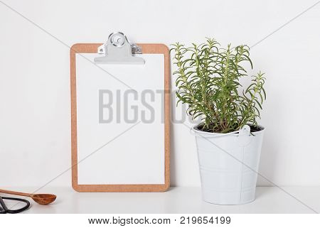 Clipboard mock-up on the table with green rosemary plant in the pot