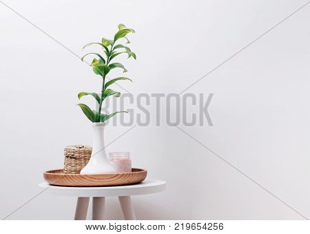 Minimalistic interior. Green plant in the vase candle and straw box on the small table at the white wall