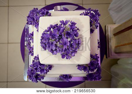 Three tiered white cake with purple flowers