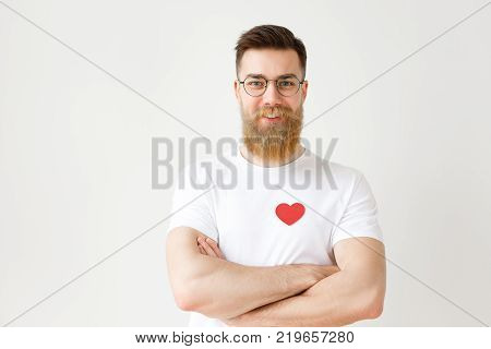 Portrait of handsome bearded young man wears round spectacles and white casual t shirt with red heart, keeps hands crossed, looks confidently into camera, isolated over white studio background