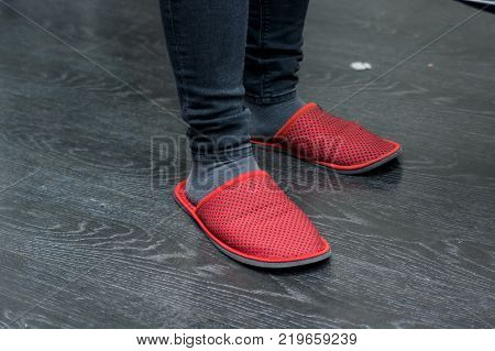 Close up dark wooden floor and feet in red slippers feeling comfortable