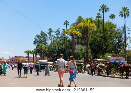 Marrakech Morocco - May 12 2017: Tourists and locals are walking on the street leading towards the famous Jemaa el Fna square in Marrakech Morocco passing by the horse-drawn carriages.