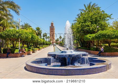Marrakesh Morocco - May 12 2017: People are sitting and relaxing next to the fountain in the Koutoubia Gardens with the view of the Koutoubia Mosque in Marrakech Morocco.