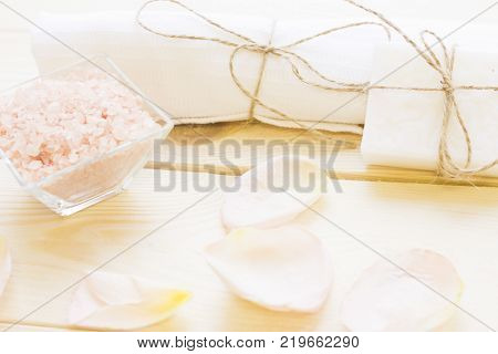 Spa and body care concept. Relaxing bath- a bowl of fragrant rose bath salt, white towels tied with a thread and pink rose petals on a wooden surface. A space for your text or product display.