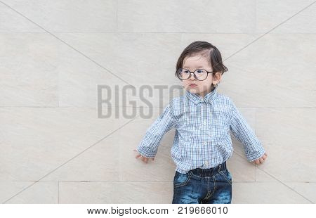 Closeup happy asian kid with eyeglasses look at the space in gentle kid concept on marble stone wall textured background with copy space