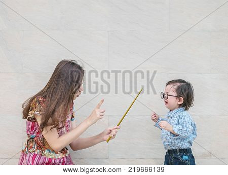 Closeup asian kid was scolded by his mother on blurred marble stone wall textured background with copy space