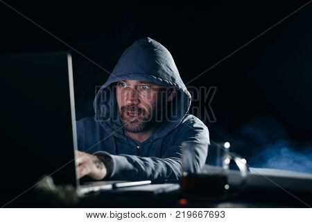 mysterious man with a beard, doing something illegal on a laptop, in the dark