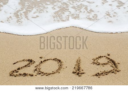 New year 2019 is written in the sand