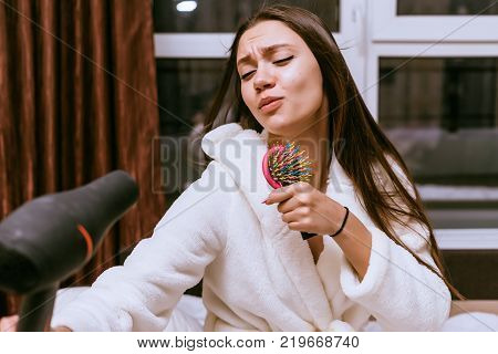 a funny young girl dries her long hair with a hair dryer, they flutter, she sings in a comb