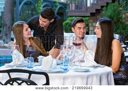 Two Couples Outdoors In Restaurant Celebrating.