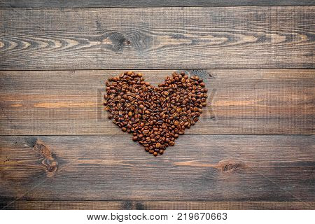 Coffee beans in heart shape on dark wooden table top view copyspace. Coffee background