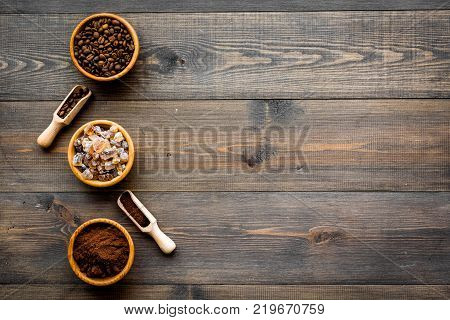 Coffee concept. Beans and grounded coffee in bowls on dark wooden background top view.