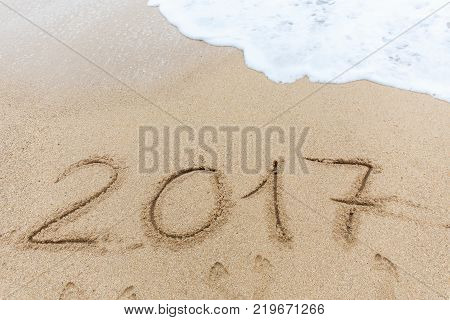 New year 2017 is written in the sand