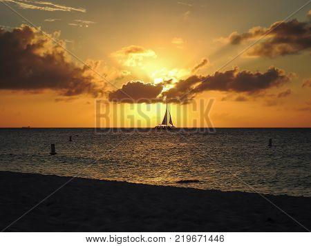 Travel photography - tropical sunset with a sailing catamaran in Aruba (Dutch Antilles).