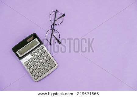glasses, calculator and wallet on wooden table.