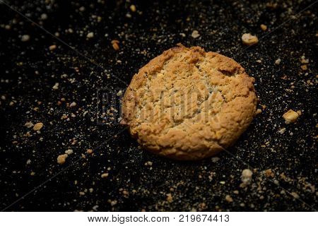 Oat cookies and many crumbs on black tablecloth