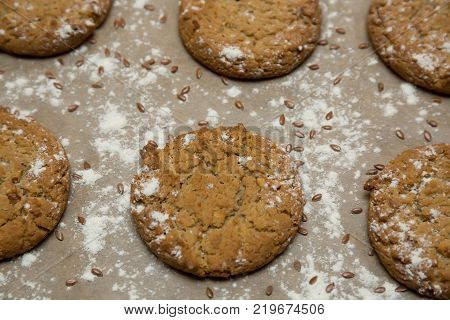 Oatmeal cookies sprinkled with powdered sugar on parchment