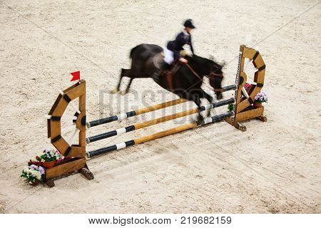 Equitation. Black horse with male rider equestrian man jumping over obstacle. Riding competition. Real.