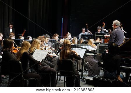 JOLIET, ILLINOIS / UNITED STATES - MARCH 20, 2016: Dr. Lawrence Sisk conducts the Metropolitan Youth Symphony Orchestra (MYSO) during a dress rehearsal prior to a concert in the Fine Arts Theater of Joliet Junior College.